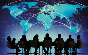 Group of silhouettes sitting around a table with world map in the background