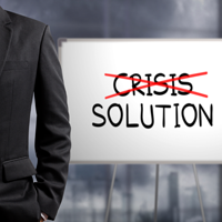 Man standing next to Crisis being striked out Solution sign